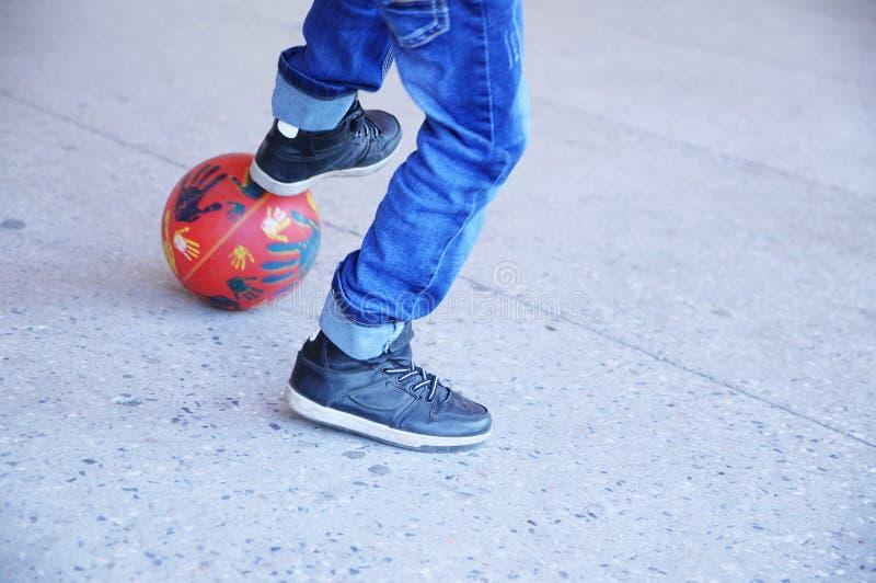 Jongens speelvoetbal, tiener` s benen met een bal op asfalt, de speler van het voetbalteam, opleidings openlucht, actieve levenss royalty-vrije stock afbeeldingen