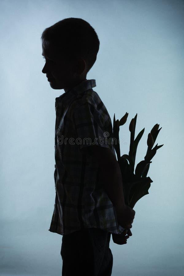 Jongens verbergend boeket van bloemen achter zich stock fotografie