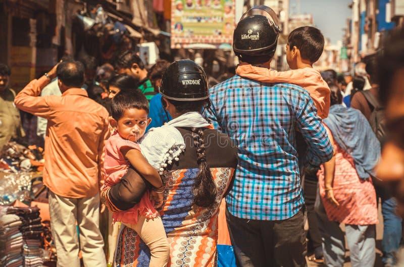 Jongens in wapens van ouders in lawaaierige menigte van de Aziatische straat stock foto's