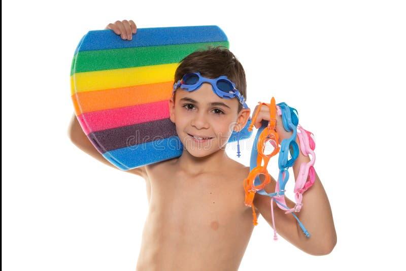 Jongensatleet met blauwe glazen op zijn hoofd, die een multicolored zwemmende raad in zijn hand en vele multi-colored glazen houd stock afbeeldingen