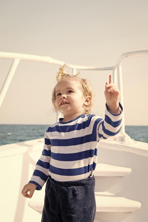 jongensconcept Zeeman Boy Jongensreis op schip in overzees Weinig jongen houdt wijzervinger opgeheven Kijk daarginds royalty-vrije stock foto