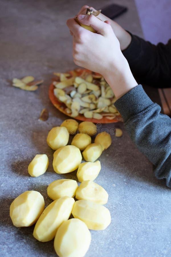 Jongenshanden die aardappels pellen royalty-vrije stock fotografie
