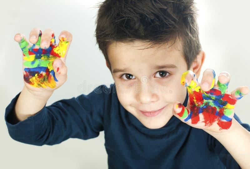 Jongenshanden met kleurrijke verf worden geschilderd die royalty-vrije stock afbeeldingen