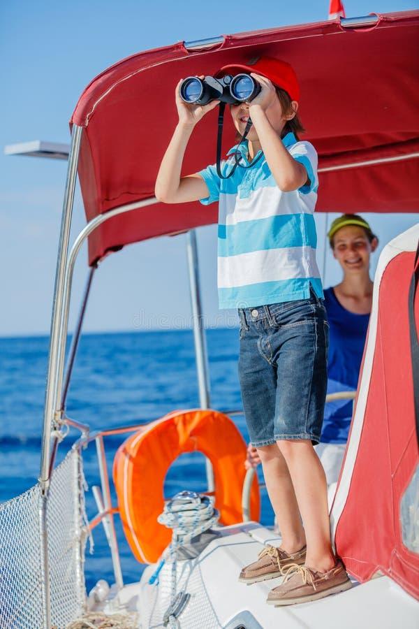 Jongenskapitein met zijn zuster aan boord van varend jacht op de zomercruise Reisavontuur, zeilen met kind op familie stock fotografie