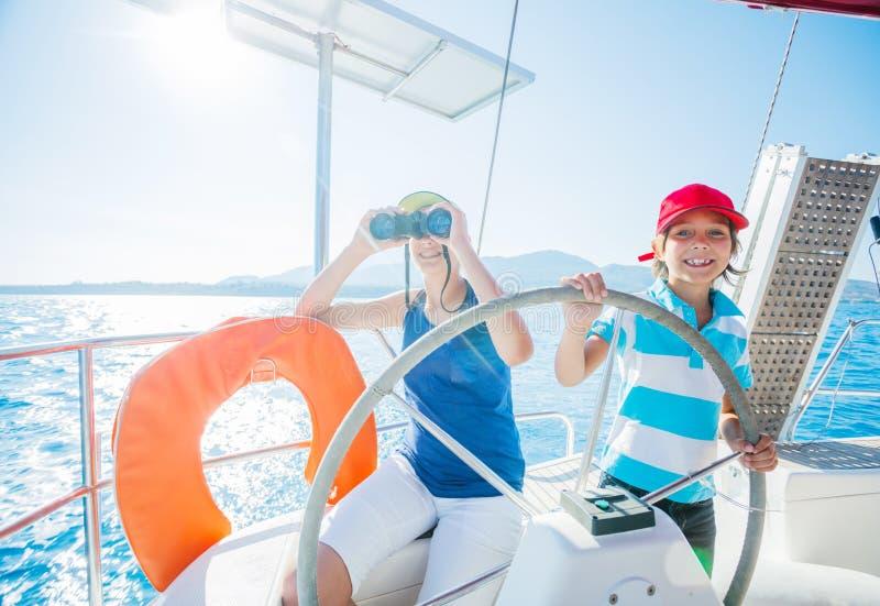 Jongenskapitein met zijn zuster aan boord van varend jacht op de zomercruise Reisavontuur, zeilen met kind op familie royalty-vrije stock foto