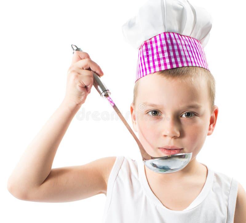 Jongenskok die chef-kokhoed met verse groenten en vruchten dragen. royalty-vrije stock fotografie