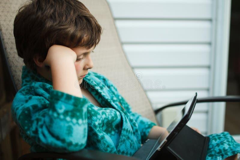Jongenslezing op een tablet royalty-vrije stock afbeeldingen