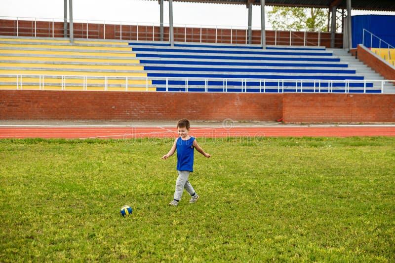 Jongenslooppas rond met de bal op een voetbalgebied stock fotografie