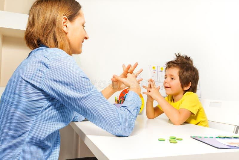 Jongensoefeningen die vingers met therapeut zetten stock afbeelding
