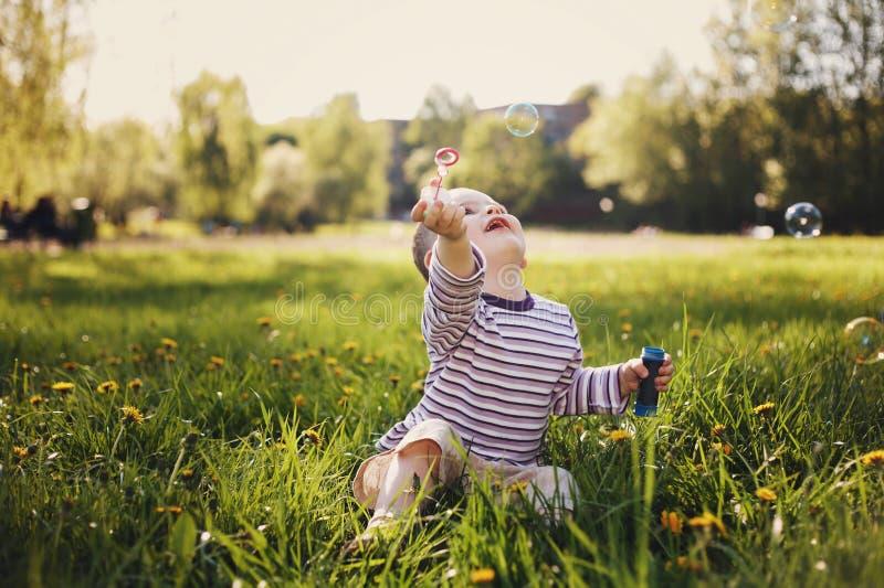 Jongensspelen met bellen in de zomerpark stock foto's