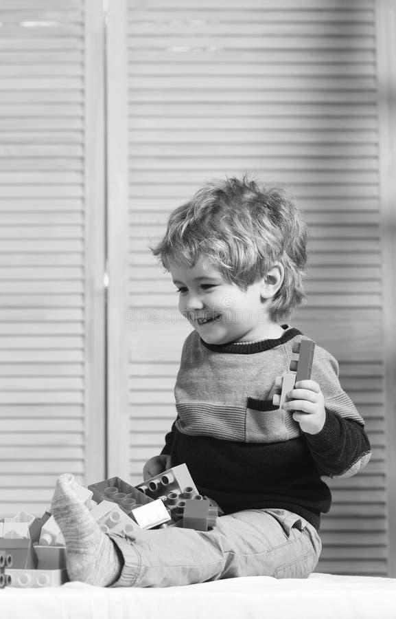 Jongensspelen met lego op houten muurachtergrond royalty-vrije stock foto