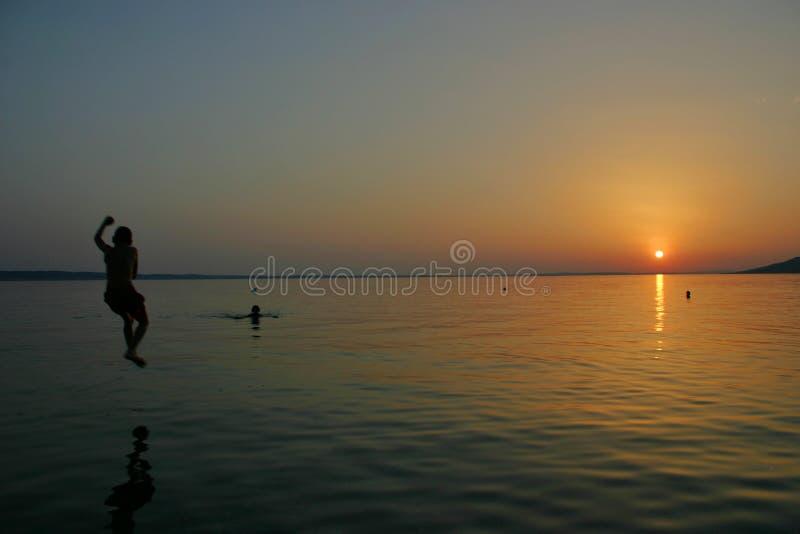 Jongenssprongen in de de overzeese kustzonsondergang van starigrad-Paklenica royalty-vrije stock afbeelding