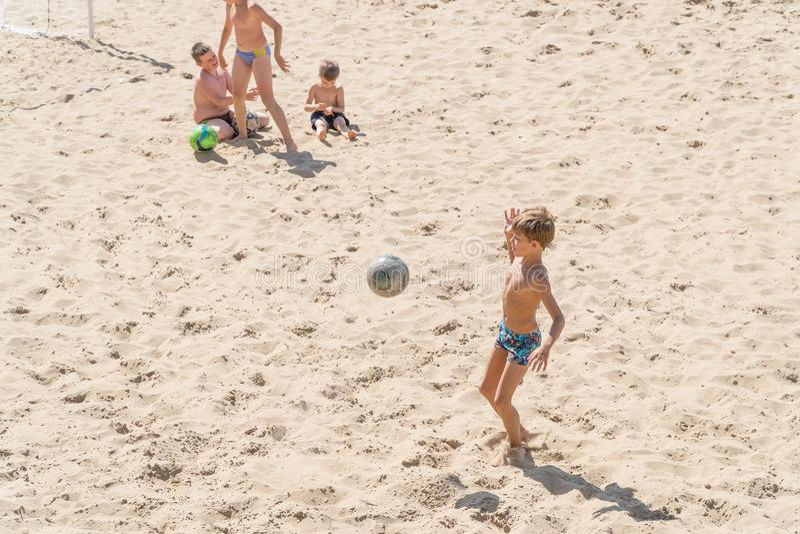 Jongenstieners die voetbal op het strand spelen royalty-vrije stock afbeelding