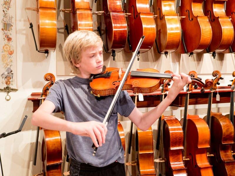 Jongensviolist Playing een Viool in Music Store stock foto's