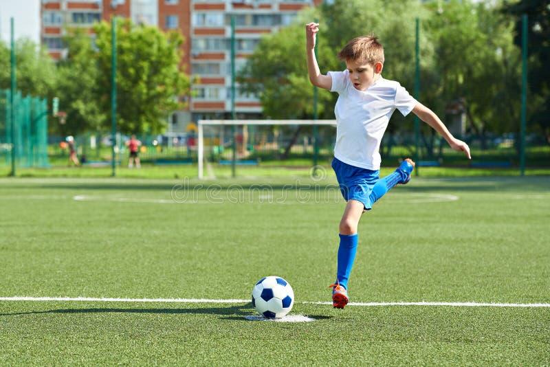 Jongensvoetballer met sprong vóór schop op bal stock fotografie
