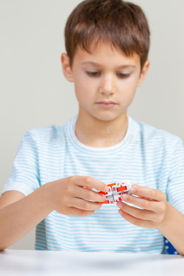 Jongenszitting bij lijst en het spelen van met vingers antistressstuk speelgoed stock foto