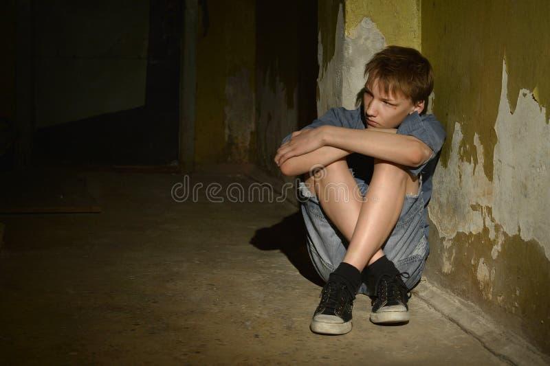 Jongenszitting in dark stock foto's