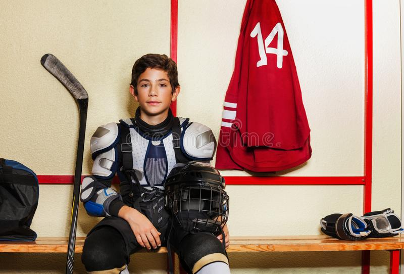 Jongenszitting op de bank in ijshockeykleedkamer stock foto's