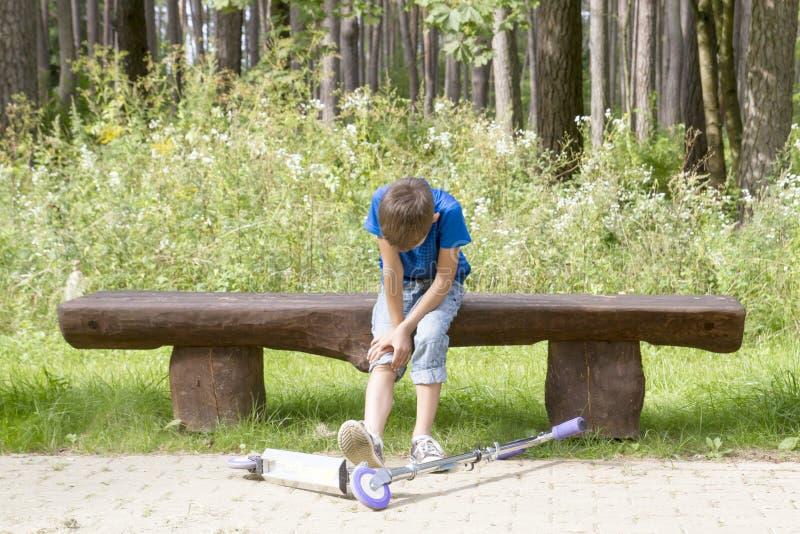 Jongenszitting op de houten bank in het park Het kind viel terwijl het berijden van zijn autoped en gekwetst been stock foto