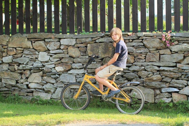 Jongenszitting op een fiets stock foto