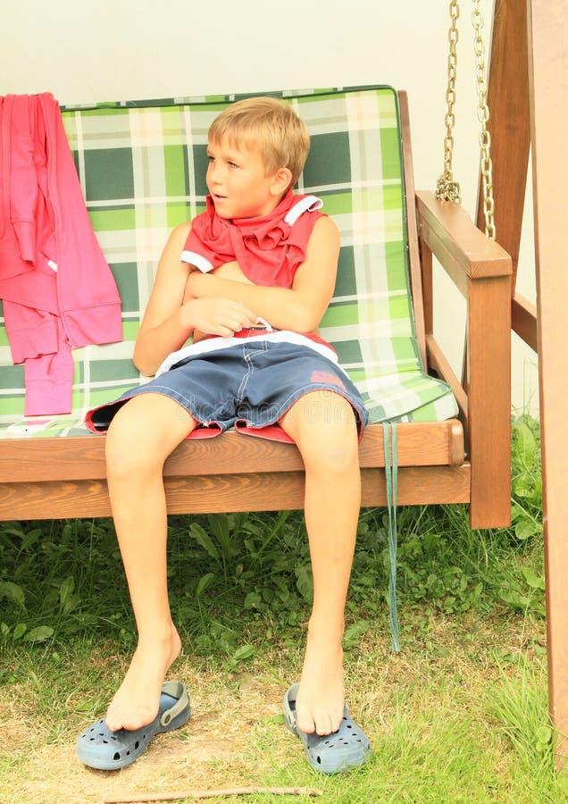 Jongenszitting op een tuinschommeling stock foto's