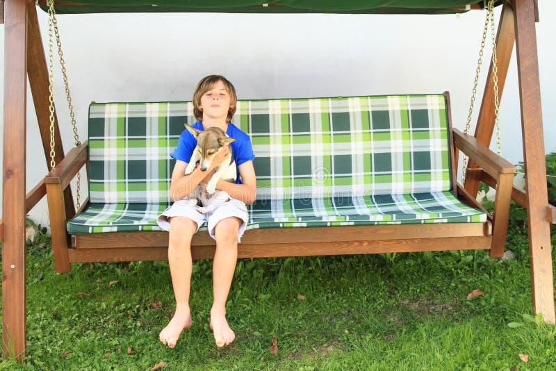 Jongenszitting op een tuinschommeling met hond stock foto