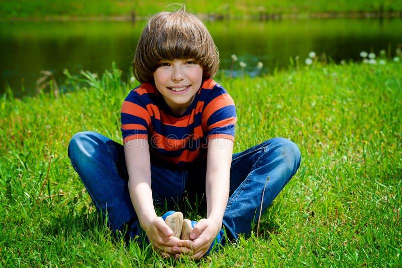 Jongenszitting op gras stock afbeelding