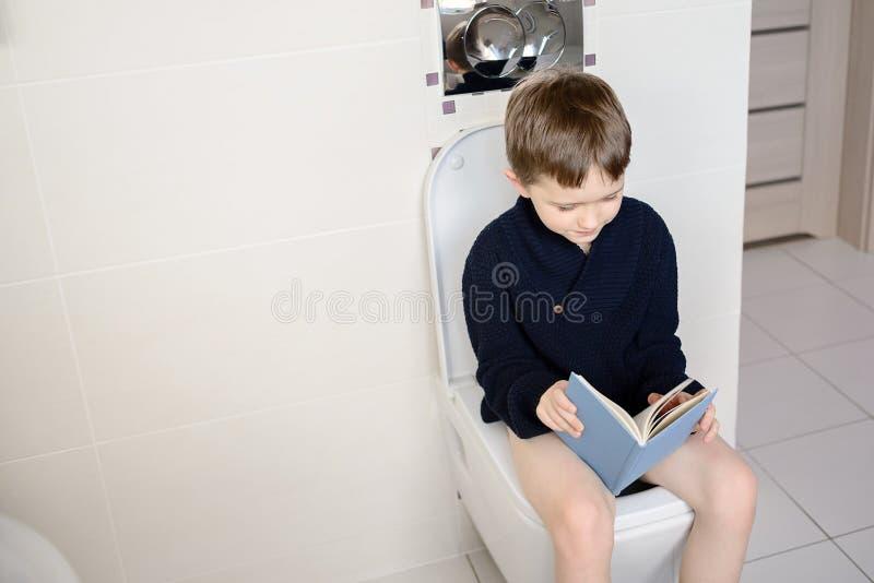 Jongenszitting op het toilet en lezing een blauw boek stock afbeelding