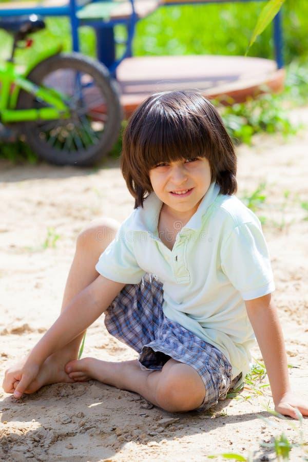 Jongenszitting op het zand royalty-vrije stock foto