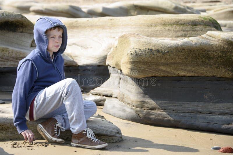 Jongenszitting op rotsen stock afbeelding