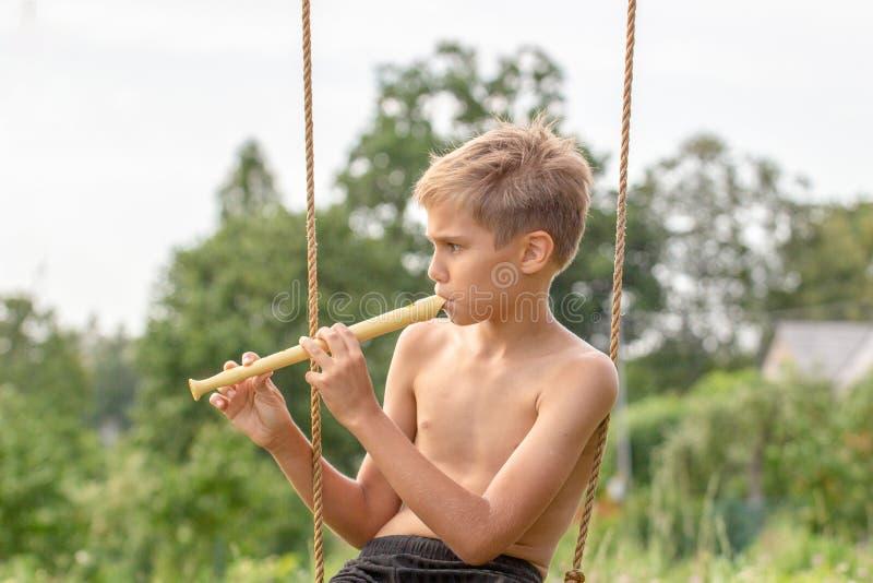 Jongenszitting op schommeling en het spelen fluit in openlucht stock afbeeldingen