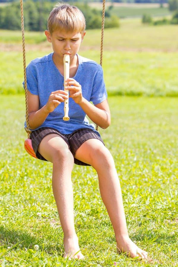 Jongenszitting op schommeling en het spelen fluit in openlucht royalty-vrije stock afbeelding