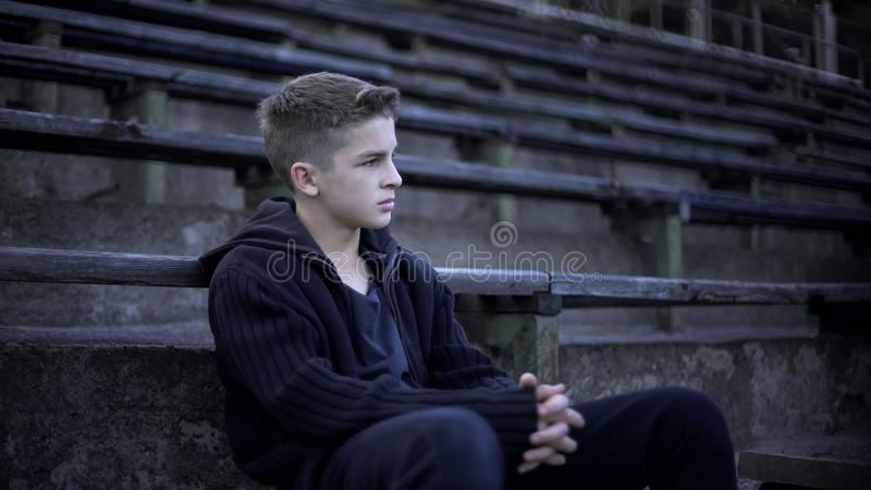 Jongenszitting op stadiontribune, verwoesting en armoede rond, stad na oorlog stock foto