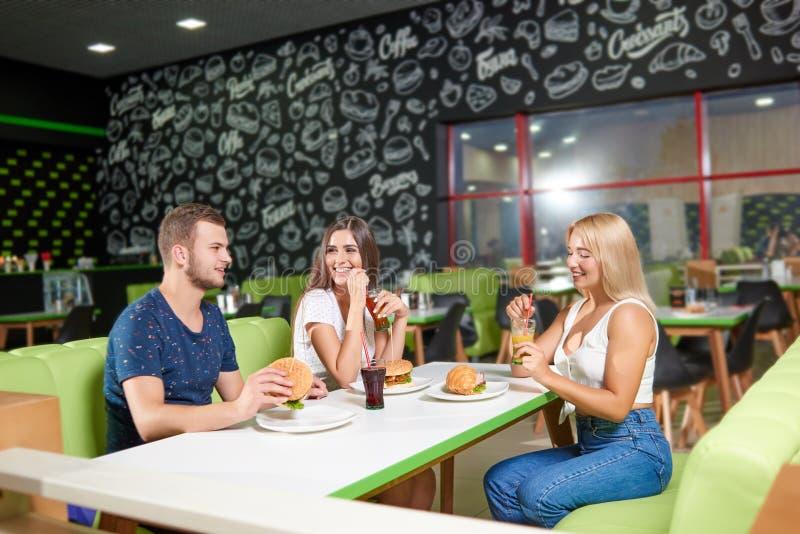Jongenszitting samen met twee meisjes en het spreken in koffie stock afbeeldingen
