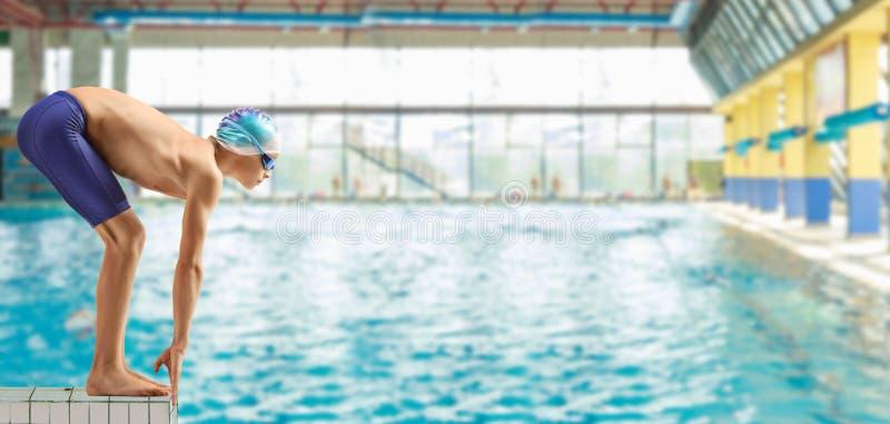 Jongenszwemmer op de beginpositie bij het zwemmen pooln stock foto