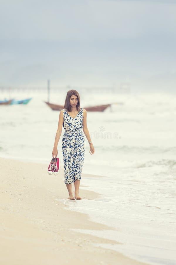 Jongere Aziatische vrouw die op overzees strand lopen stock afbeelding