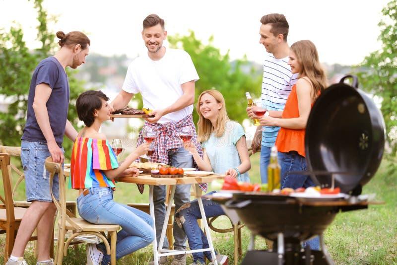Jongeren die barbecue met moderne grill hebben stock afbeelding