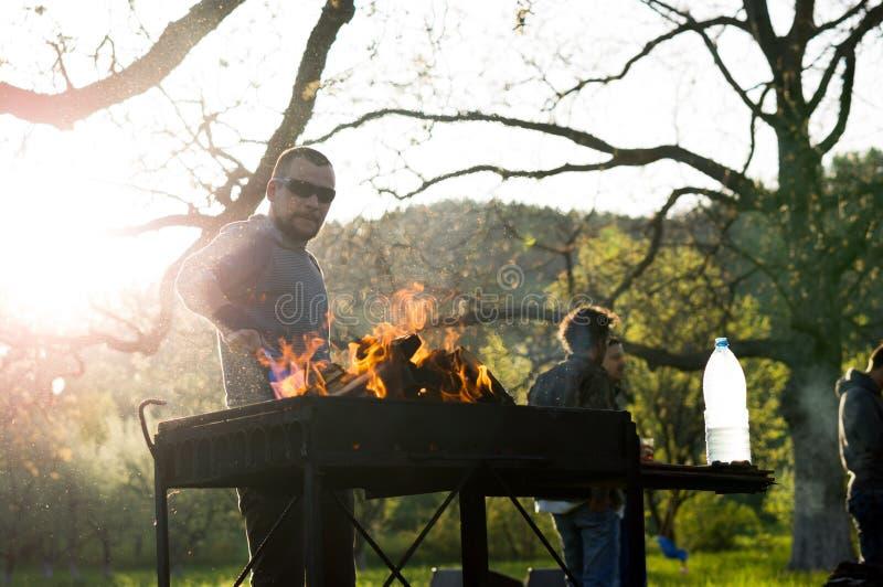 Jongeren die barbecue uit in de tuin op arbeidsdag hebben royalty-vrije stock afbeeldingen
