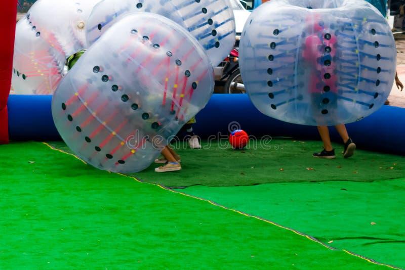 JONGEREN DIE BUMPERBALL IN OPENLUCHT SPELEN stock foto's