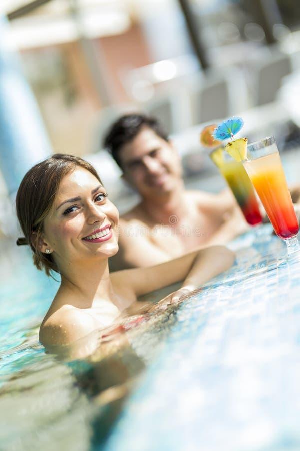 Jongeren die cocktails drinken door het zwembad en relaxin stock fotografie