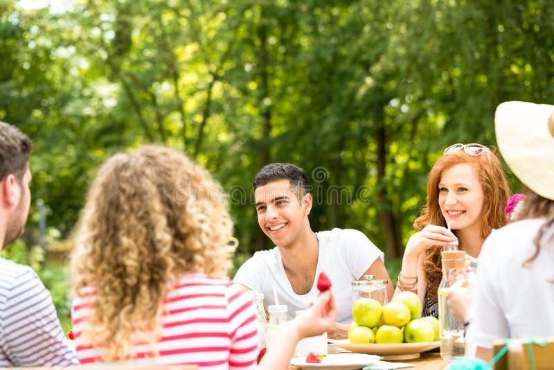 Jongeren die in de tuin en het besteden tijd samen zitten stock afbeelding