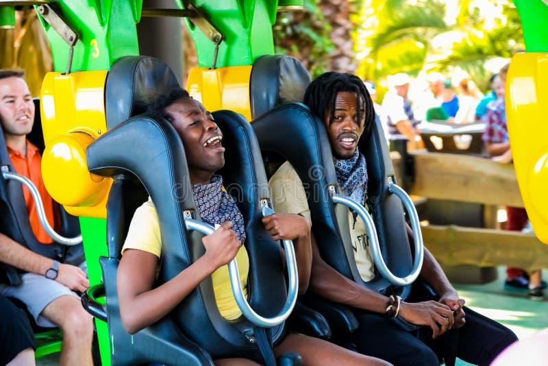 Jongeren die een achtbaan berijden bij een themapark royalty-vrije stock foto's
