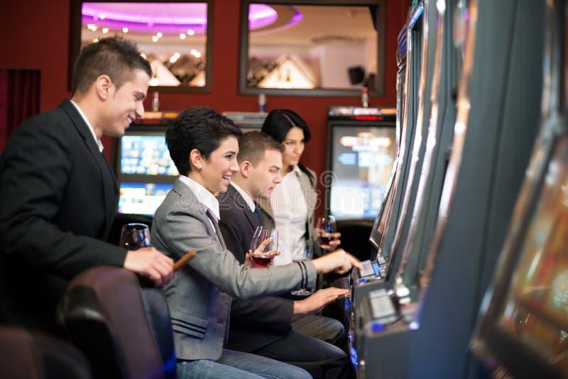 Jongeren die in het casino op gokautomaten gokken royalty-vrije stock fotografie
