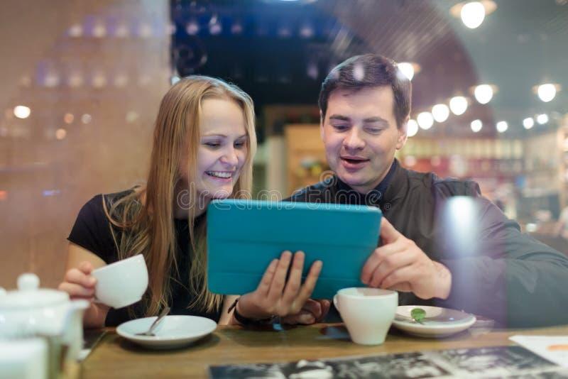 Jongeren die koffie drinken en op stootkussen kijken stock afbeeldingen