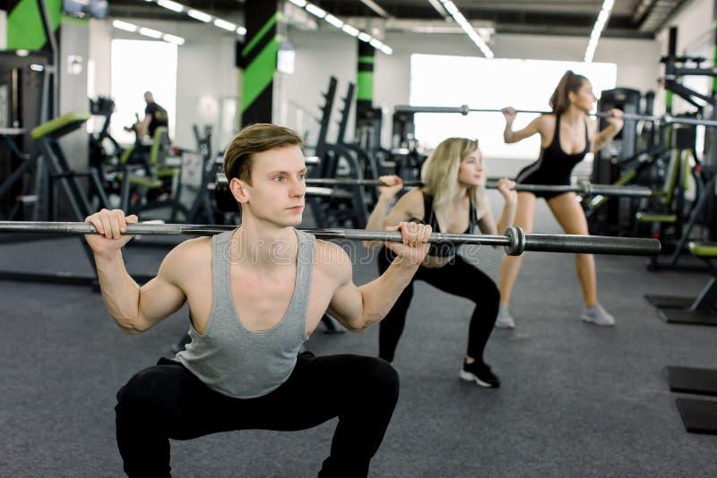Jongeren die met barbells bij gymnastiek uitwerken De aantrekkelijke vrouwen en de knappe spierman trainer leiden in licht op royalty-vrije stock foto
