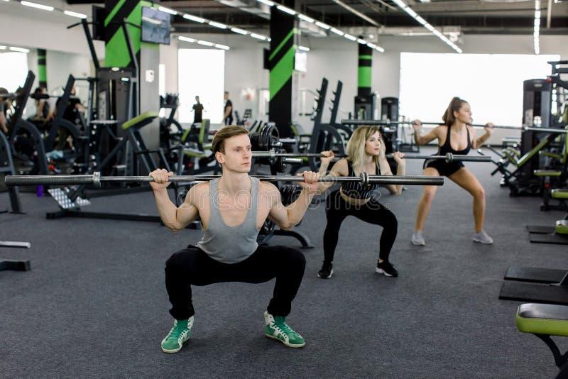 Jongeren die met barbells bij gymnastiek uitwerken De aantrekkelijke vrouwen en de knappe spierman trainer leiden in licht op stock foto's
