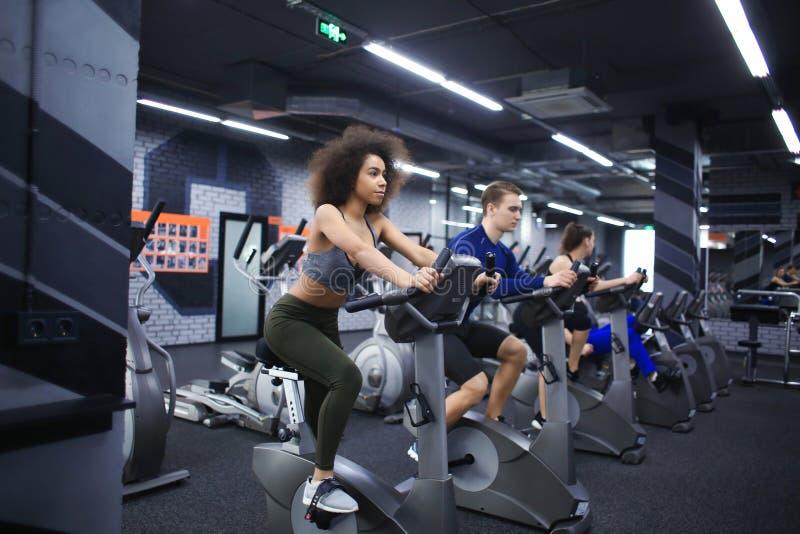 Jongeren die oefeningen op elliptische trainer in gymnastiek doen stock afbeelding