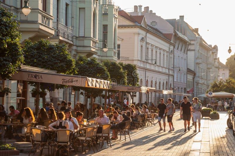 Jongeren die op een voetstraat van Szeged, Zuidelijk Hongarije, met andere mensen lopen die op lijsten in koffie & restaurant zit stock fotografie