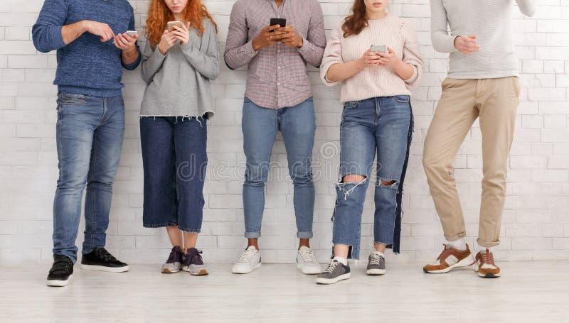Jongeren die op hun smartphones texting, die op muur leunen royalty-vrije stock afbeeldingen