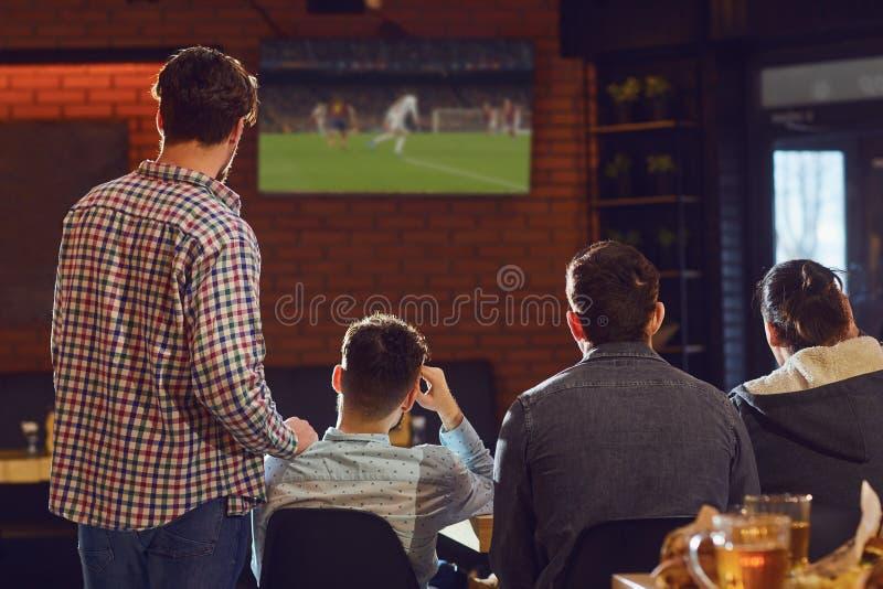 Jongeren die op voetbal op TV in de bar letten royalty-vrije stock foto